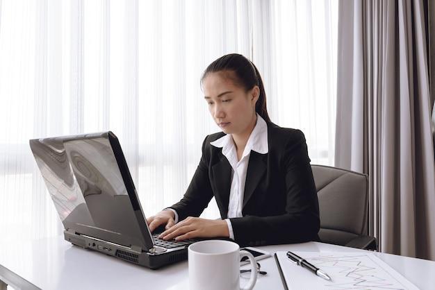 Деловая женщина, используя портативный компьютер в офисе