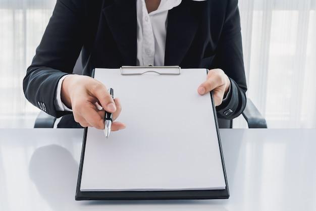 若い女性はスーツで彼のオフィスでは、保険ポリシーを示して、ペンで指してどこポリ
