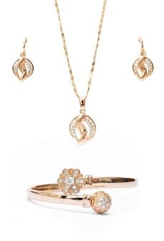 ゴールドネックレスのブレスレットと耳のリングジュエリーは、白の背景に