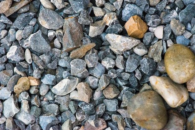 コンクリートの石の背景、小石の白い真珠の女性のエンパワーメントとコンクリートの石のクローズアップ