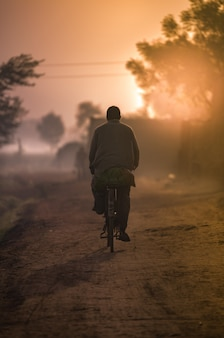 村の夕日、自転車に乗る男