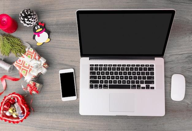 Компьютерный ноутбук мобильный дисплей на столе с изолированным белый экран для макета в рождество