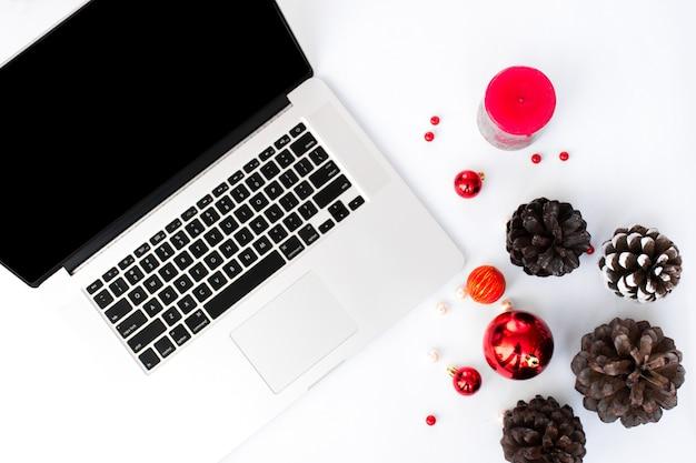 Компьютерный ноутбук мобильный дисплей на столе с изолированным белый экран для макета в рождество. рождественская елка, подарки, украшения в фоновом режиме.