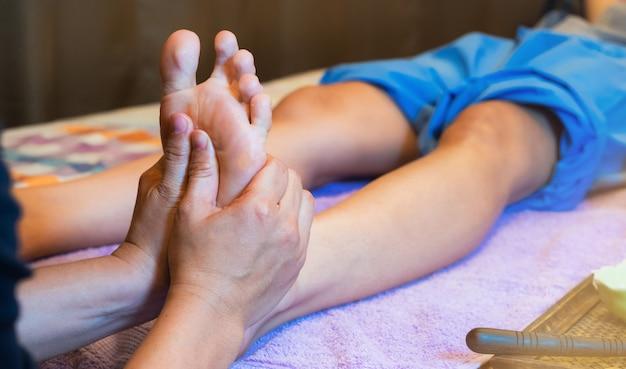 足のマッサージをしている女性の手のクローズアップ。足のマッサージ