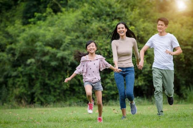 Концепция семейного отдыха. азиатская семья играет в саду