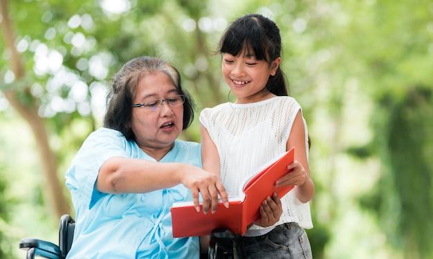 祖母と孫娘は庭で楽しんだ。アジアの家族の概念