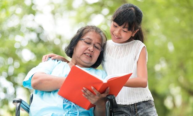 祖母祖母と孫娘が庭で楽しんだ。アジアの家族の概念