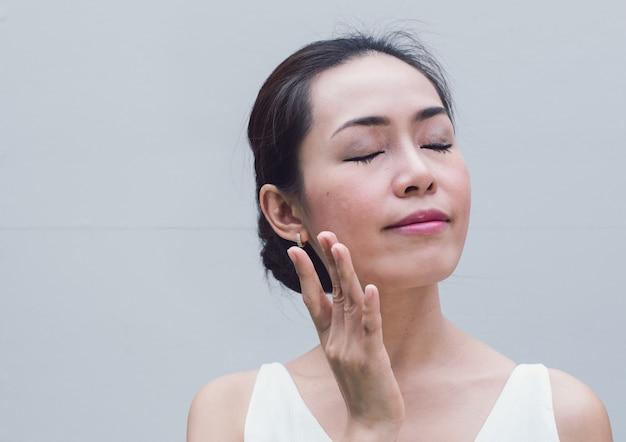 彼女のきれいな顔に保湿クリームを適用する若い女性のアジアの肖像画。