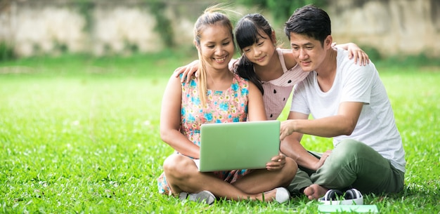 Азиатская семья: портрет семьи азиатских играть планшетный пк в в парке.