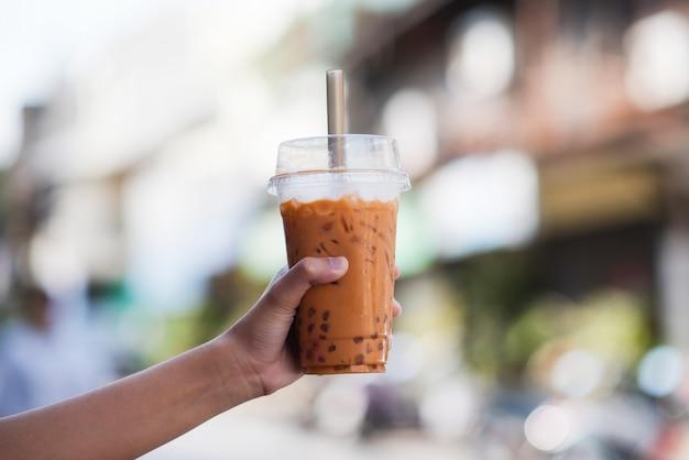 ぼかしの背景を持つ台湾アイスバブルミルクティーのプラスチックガラスを持っている手、