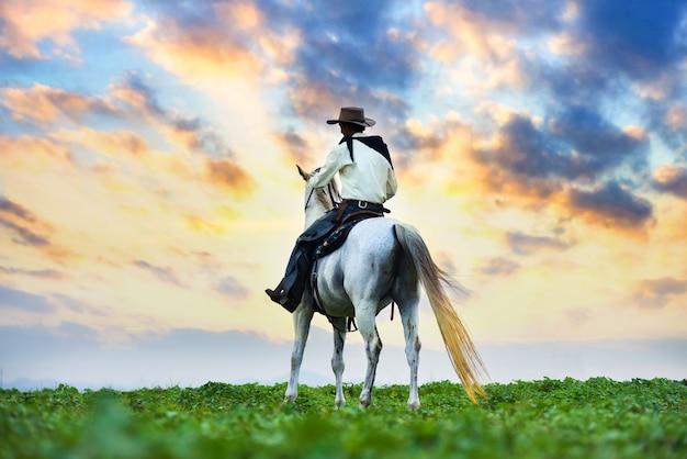 馬に乗ったカウボーイ。牧場