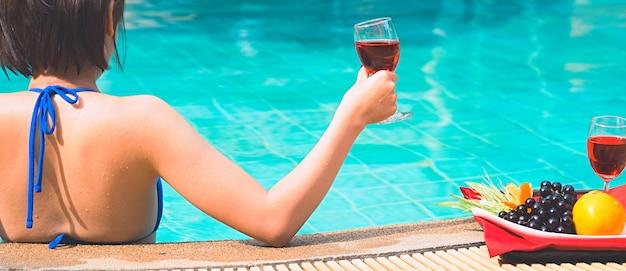 幸せな女の子が遊んで、夏休みの間にプールでリラックス