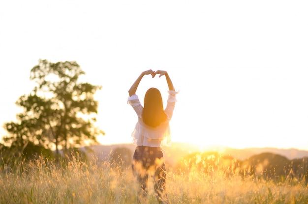 Девушка, наслаждаясь природой на поле. солнечный свет. свечение солнца. свободная счастливая женщина