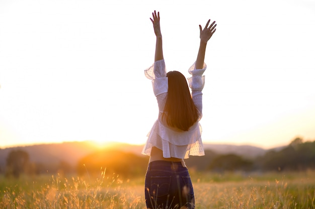 フィールドで自然を楽しんでいる女の子。太陽の光。グローサン。無料の幸せな女
