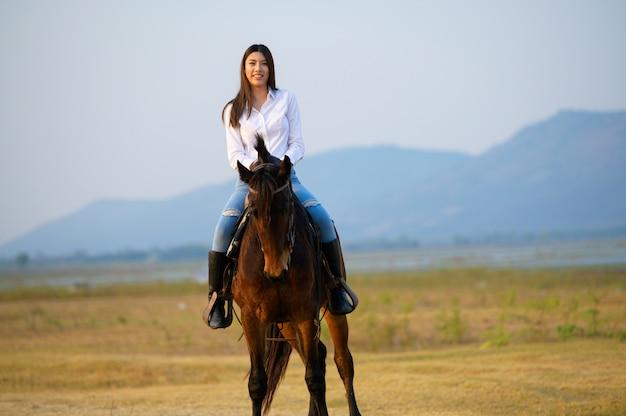広いオープンフィールドと山を見下ろす後ろからの乗馬