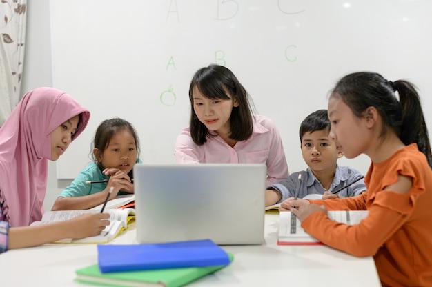 アジアの小学生。アジアの女性教師が子供たちに教えています。