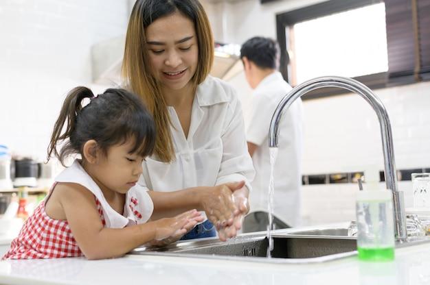 Мать и дочь азиатка моют руки с мылом в раковине кухни