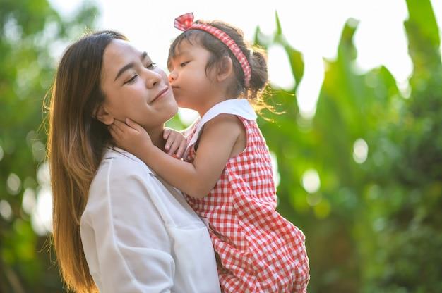 Мать и маленькая дочь, играя вместе в парке. счастливая мама и дочь