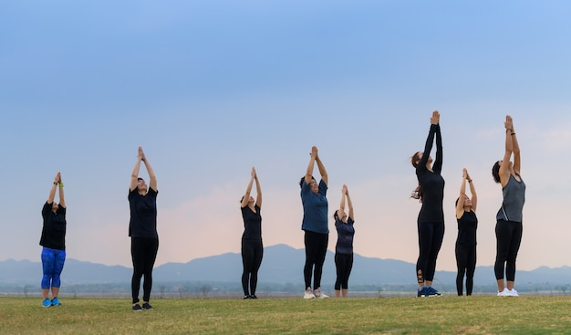 Группа женщин йоги на закате озера