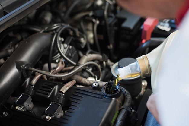 自動車整備士が新鮮な潤滑油エンジンオイルを充填する
