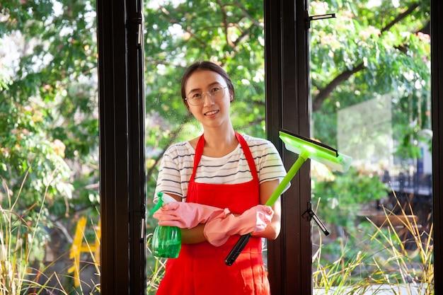 ナプキンクリーニングウィンドウを持つアジアの女性。洗浄スプレーで窓のガラスを洗います。