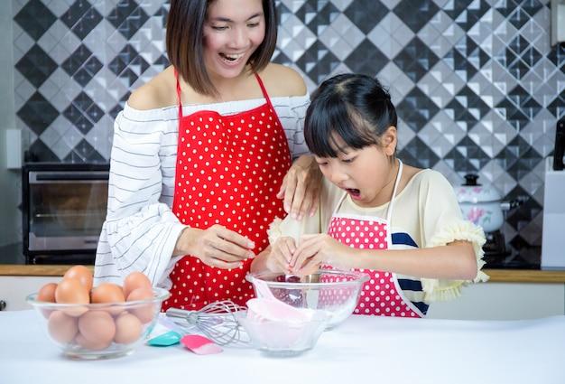 美しい母は娘が台所で生地を準備することを教えます。概念家族は幸せです。