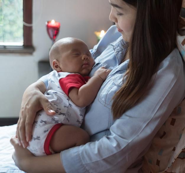 母親の母乳と抱きしめる赤ちゃん。彼女の生まれたばかりの子供を授乳している若いお母さん。