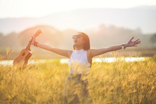 夕日を楽しんで無料の幸せな女。平和、自然の静けさを楽しんでいる空で育った腕と広げた顔で夕日の黄金の太陽の光の輝きを受け入れる白いドレスを着た美しい女性