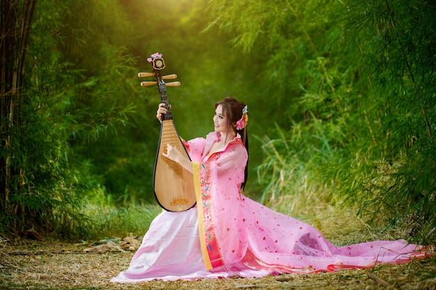 Традиционное китайское традиционное платье играет традиционная китайская пипа