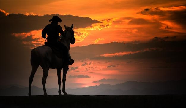 馬に乗ってシルエットカウボーイ。牧場