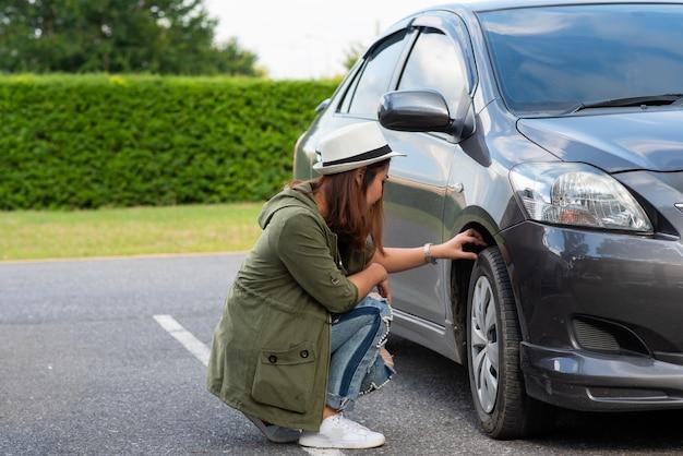 Автомобиль спущенная шина. женщина со сломанным спущенным автомобилем посреди улицы