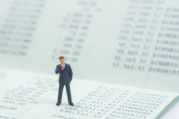 Бизнес-миниатюра стоя на фоне банковского банка