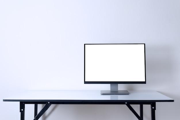白いテーブルの作業スペースの背景にコンピュータのモニター