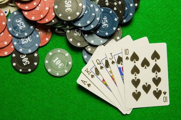 Игральные карты «королевский флеш» и фишки на зеленом фоне