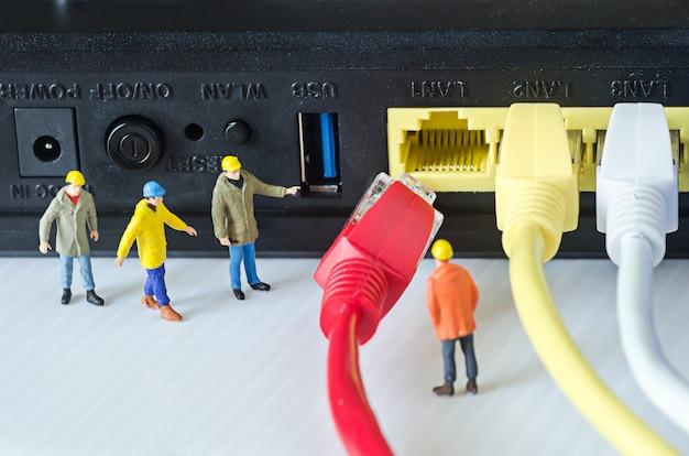 ミニエンジニアチームがイーサネットケーブルをポートに接続しようとしています