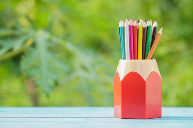 緑色の背景でボックスの色鉛筆