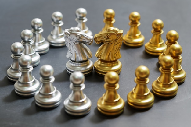 黒の背景に金と銀のチェス、ナイトに焦点を当てる