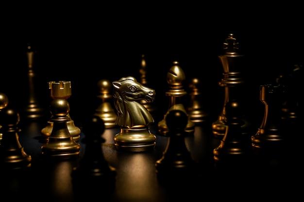 黒の背景に金のチェス、騎士に焦点を当てる