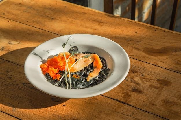 Обжаренные черные спагетти с лососем на столе.