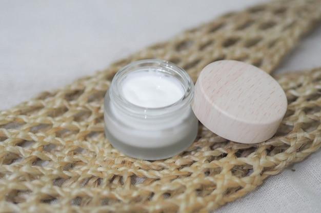 化粧品ボトルコンテナーホワイト製品と織りハンドバッグ。