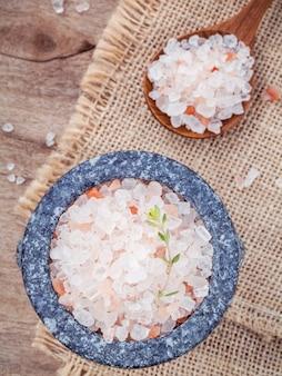 麻の袋の背景にモルタルのヒマラヤのピンクの塩。
