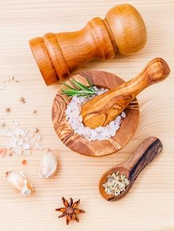 ヒマラヤのピンクの塩を木製のモルタルと木製の背景にハーブで閉じます。