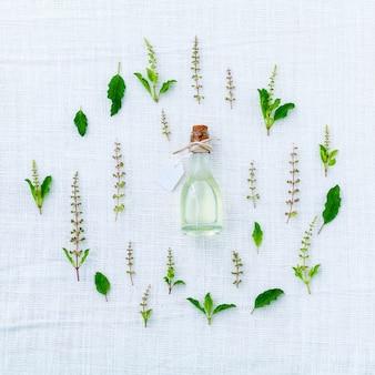 新鮮な聖バジルの花の輪と白い布の背景に葉。