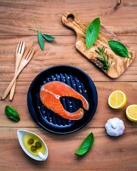 Сырое филе лосося с ингредиентами на деревянном фоне.