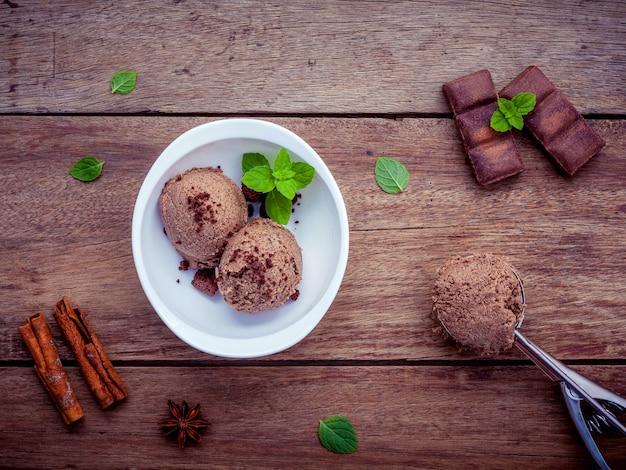 木製の背景に新鮮なペパーミントの葉のセットと白いボウルのチョコレートアイスクリーム。