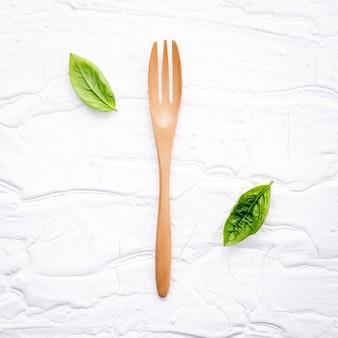 クローズアップ、新鮮な甘いバジルは、白い木製の背景にフォークを残します。
