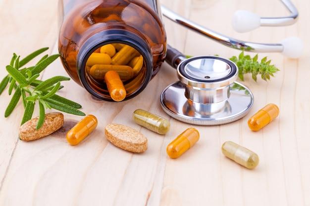 聴診器の木製の背景と漢方薬のカプセル。