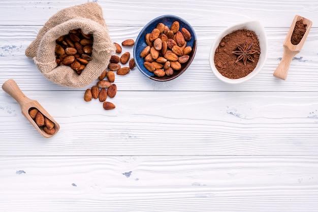 ココアパウダーとカカオ豆の木製の背景。
