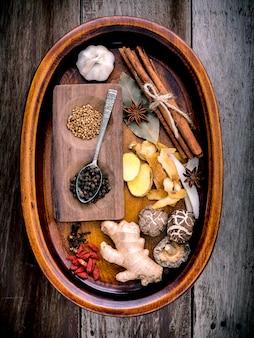 ぼろぼろの木製の背景に中国のハーブスープのための原料。