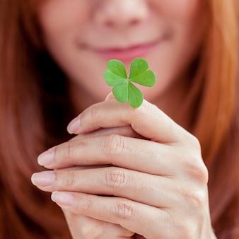 女の子はクローバーの葉を握る